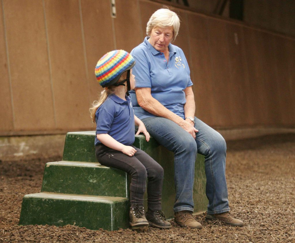 helper and rider sitting on mounting block in conversation
